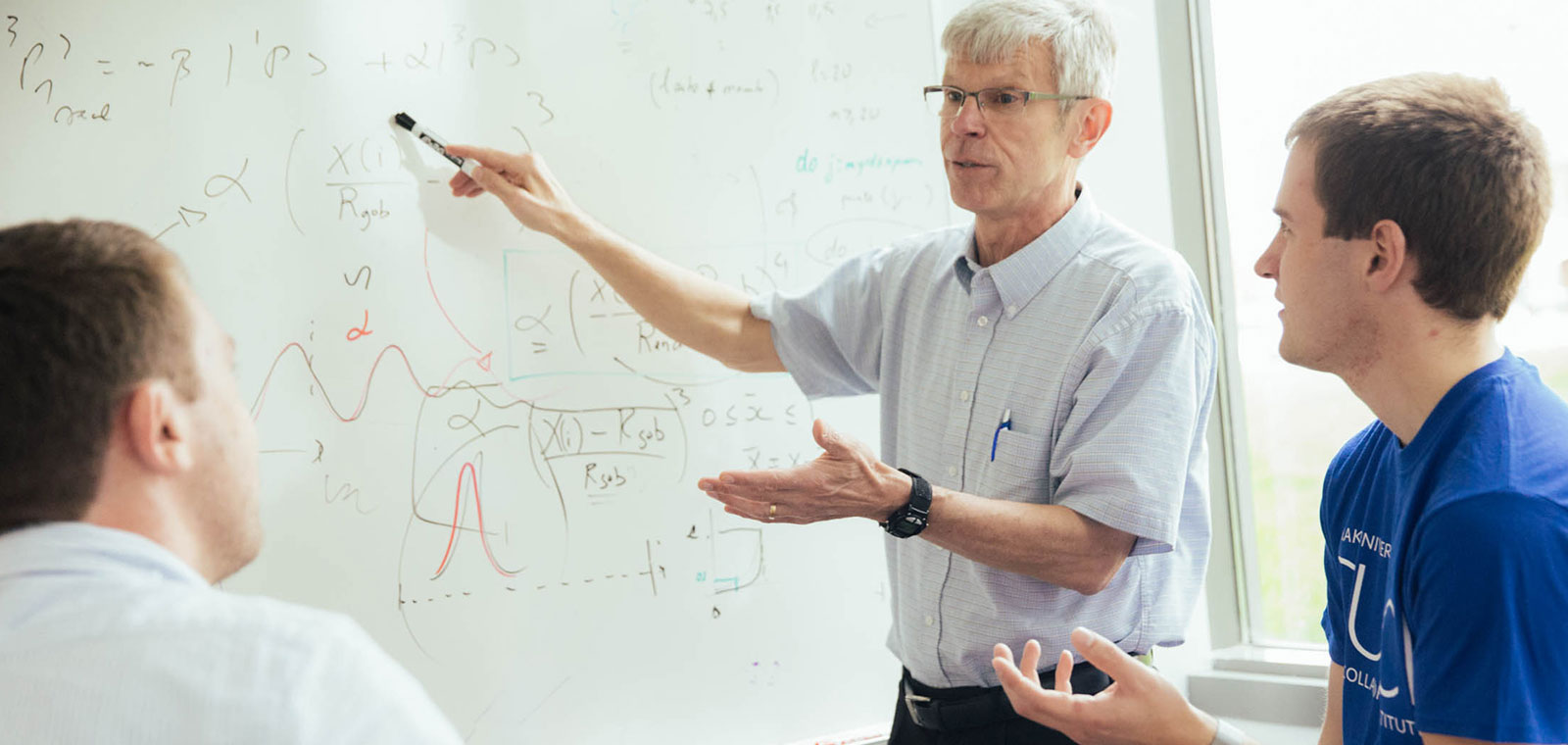 Instructor standing at a whiteboard teaching two students